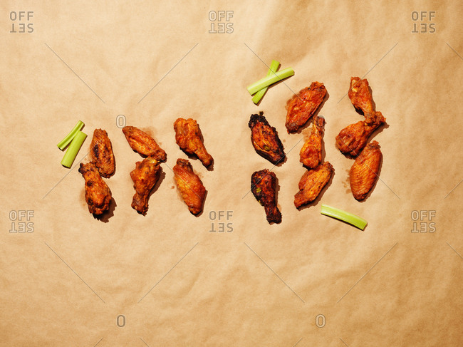 Chicken wings and celery arranged on brown paper