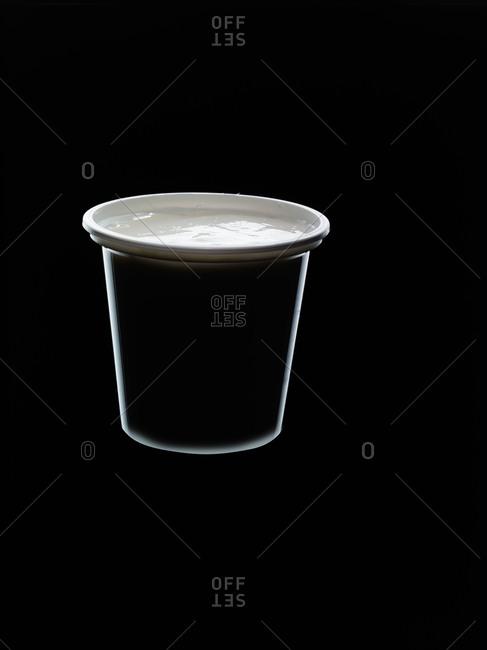 Backlit yogurt container on black background