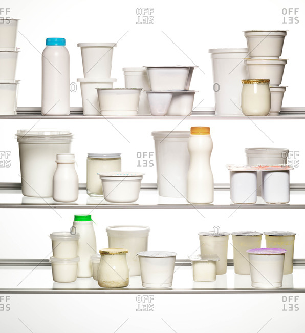 Yogurt containers of different sizes and shapes on glass shelves