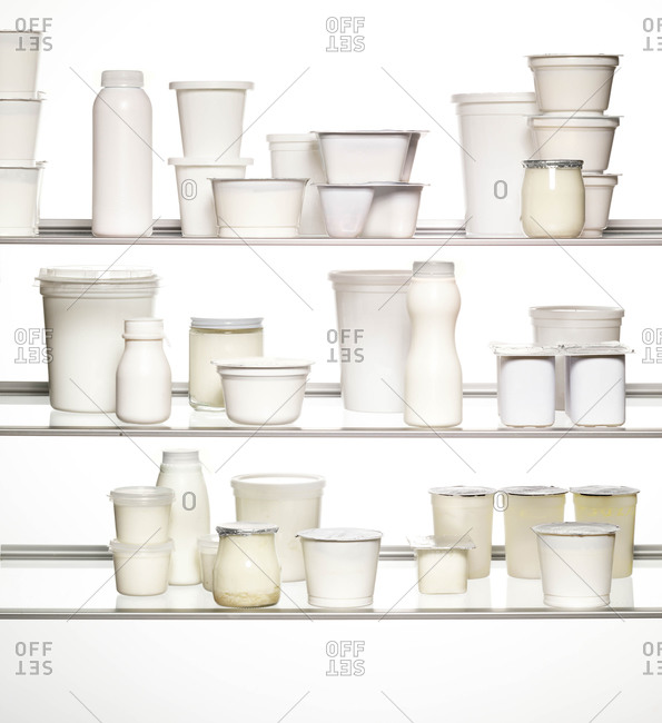Three glass shelves of different kinds of yogurt containers