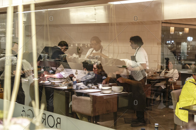 Santiago, Chile - September 26, 2014: Server with patrons in Chilean upscale restaurant