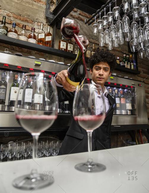 Santiago, Chile - September 23, 2014: Man pouring wine at wine bar in Santiago, Chile