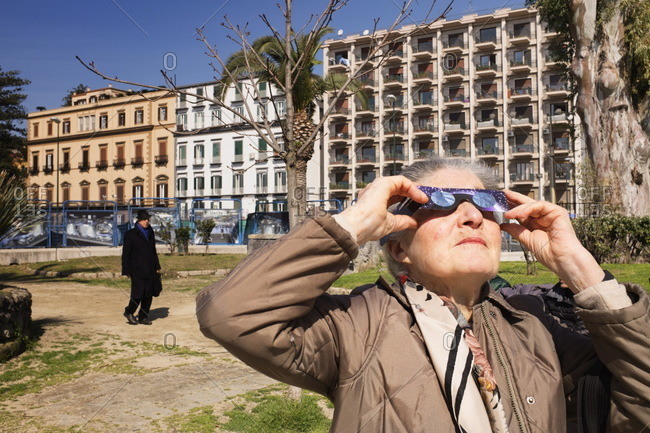 Naples, Italy - March, 20th 2015: Old woman watching solar eclipse