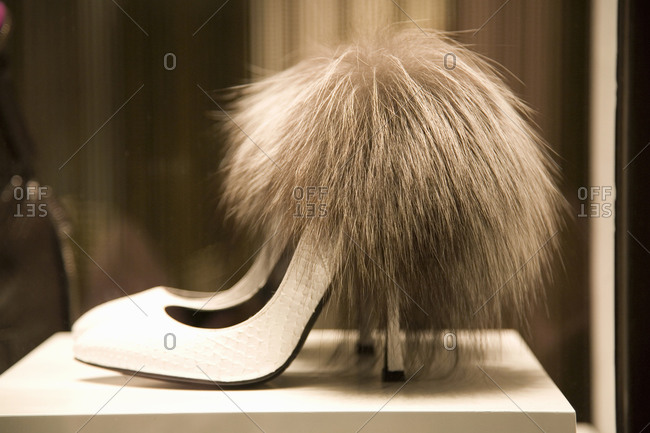 Furry high-heeled shoes on display in a store window, Milan, Italy