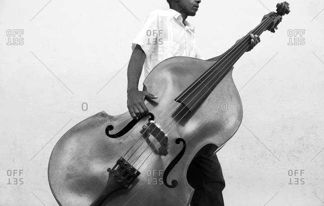 Musician carrying a double bass in Havana, Cuba