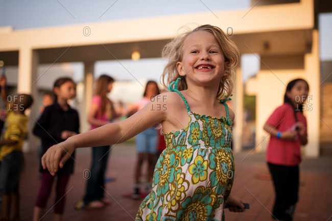 Young girl standing on scooter smiling with excitement