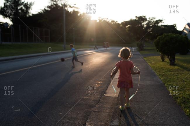 Children playing at sunset on neighborhood side street