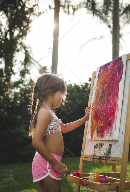 Girl painting with her fingers at an easel in backyard