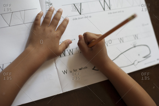 Child practicing writing letters in a handwriting book