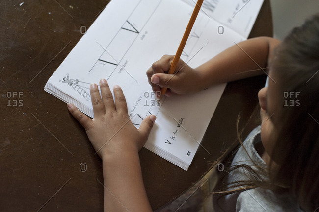 Girl writing letters in handwriting book