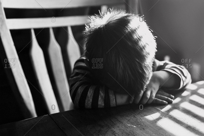 Boy with his head on table in morning