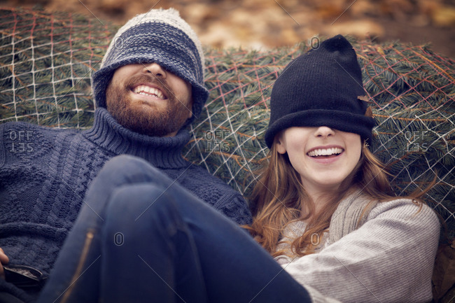 Smiling couple wearing their hats over their eyes