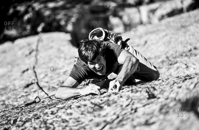 A rock climber struggles on a vertical rock wall