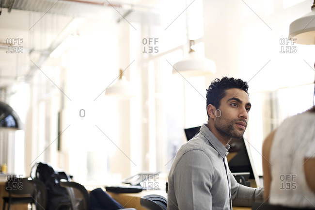 Office worker talking to his colleague in a bright open workplace