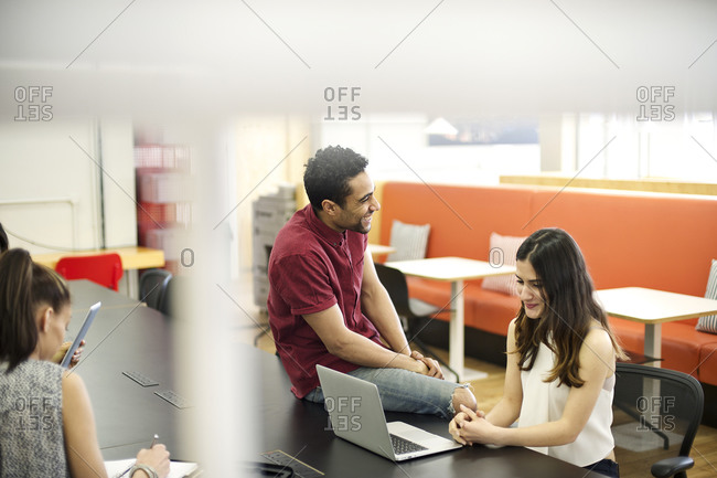 Man socializes with his co-worker in an open office