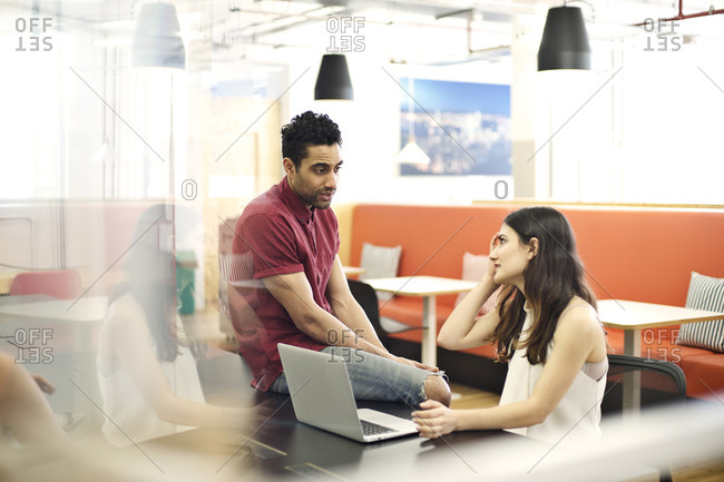 Man having a conversation with a co-worker in an open office