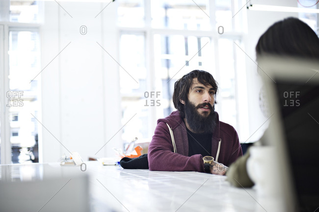 Bearded man in hoodie talking to co-worker at a conference table