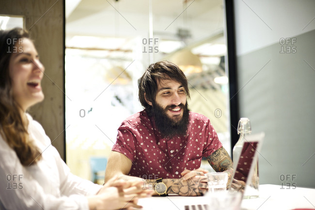 Co-workers laughing while seated around meeting table