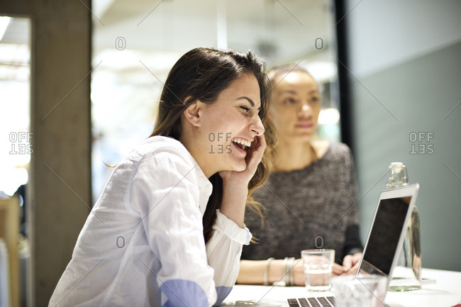 Young woman laughs while in meeting with co-workers