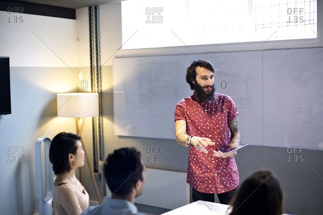 Man giving a presentation to his co-workers in a meeting room