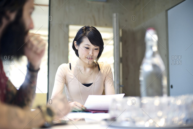 Woman reviewing a document at table with colleague