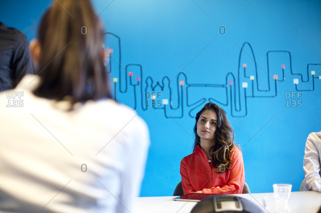 Woman listening to her colleague in a conference room at a creative agency