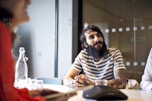 Bearded young man with tattoos listens to his colleagues in a meeting