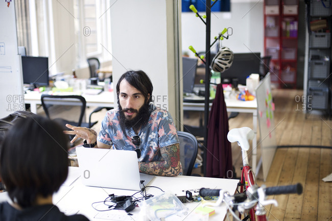 Man talks to his co-worker in a creative agency office