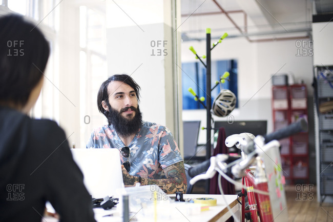 Man sitting at a desk in a creative agency office