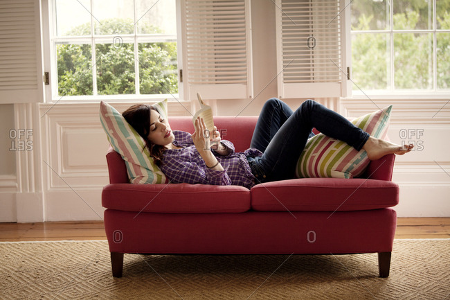 A young woman reads a book on a loveseat