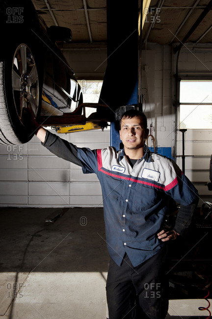 A car mechanic under a lift