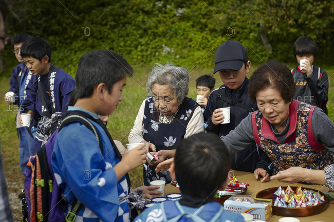 October 3, 2014: Elderly women handing out refreshments to children during a festival in Tsumago-juku, Japan