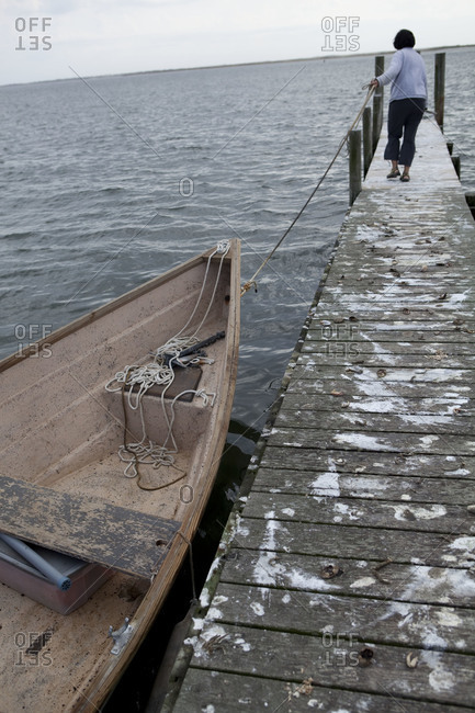 A fisherwoman walks up a dock littered with marine animal remnants