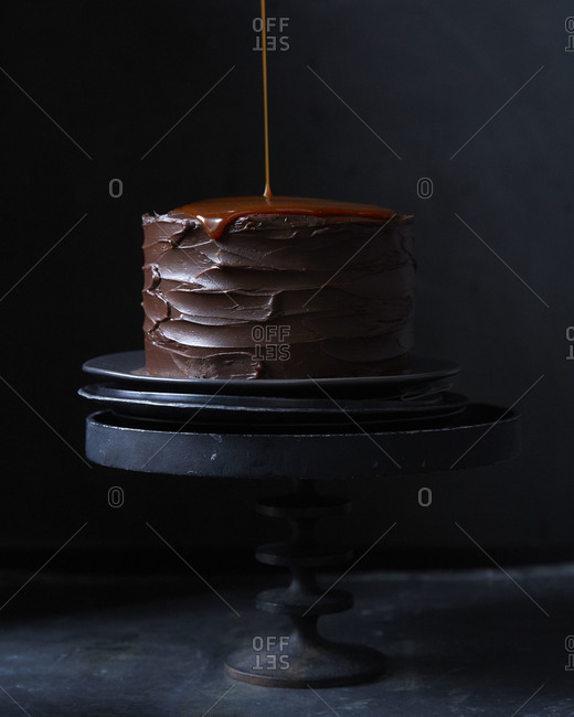 Carmel sauce pouring off the edge of a chocolate cake