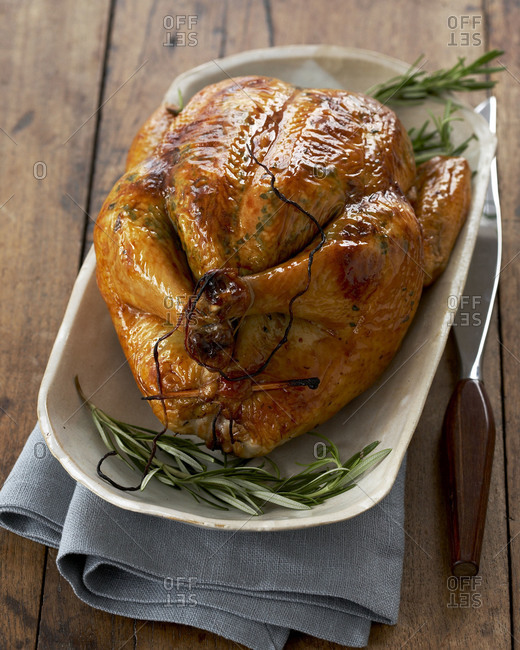 A whole chicken on a plate seasoned with rosemary