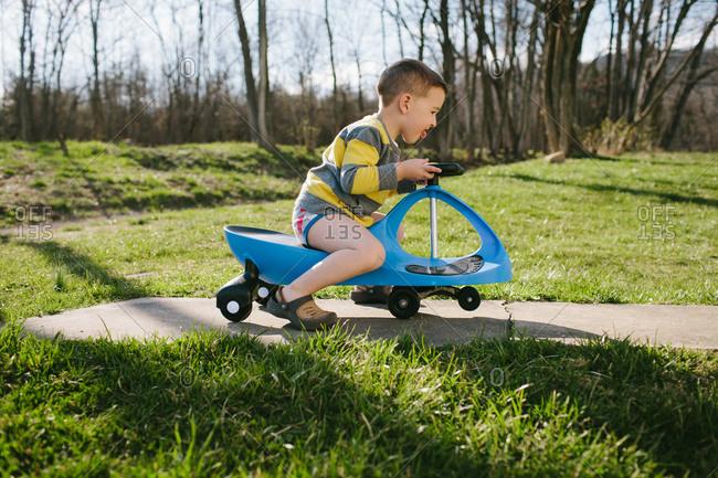 Boy riding swivel scooter outside in underwear