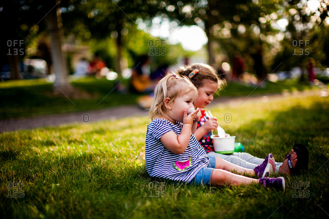 Two little girls sitting in grass eating ice cream