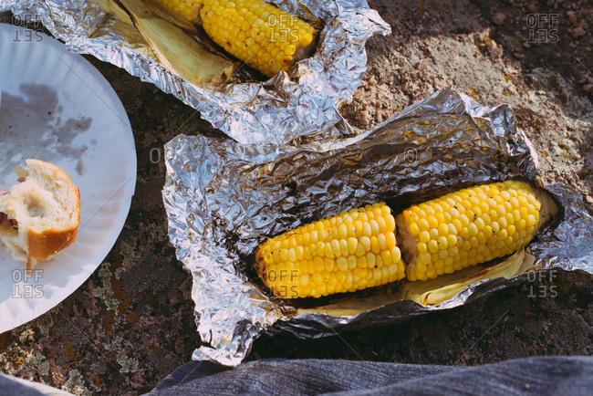 Whole corn cooked in tinfoil outside
