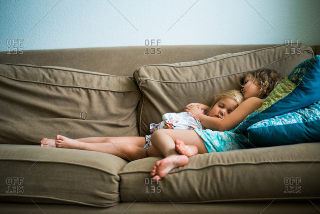 Two little girls cuddling asleep on couch