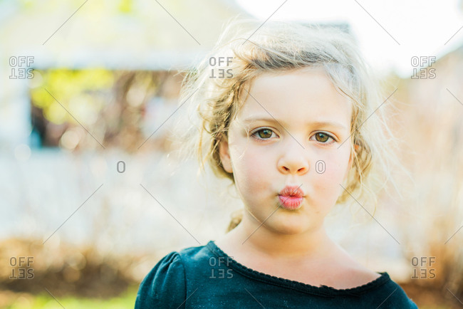 Portrait of young girl whistling in yard