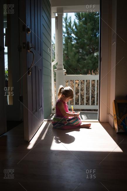 Girl in sunlight in doorway drawing