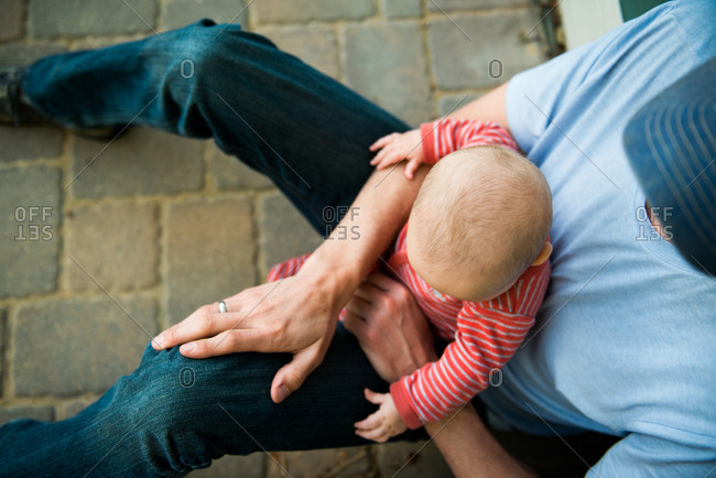 Dad holding toddler in lap outside home