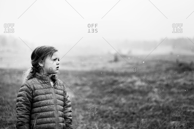 Young girl standing outside in wet, snowy field
