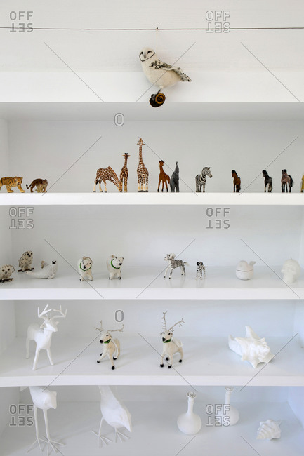 A collection of animal figurines on white shelves