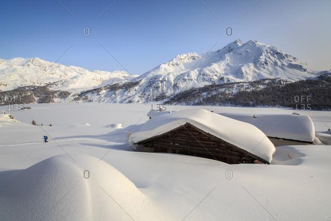 Some Spluga huts near the Maloja Pass submerged in snow on a clear winter day, Graubunden, Swiss Alps