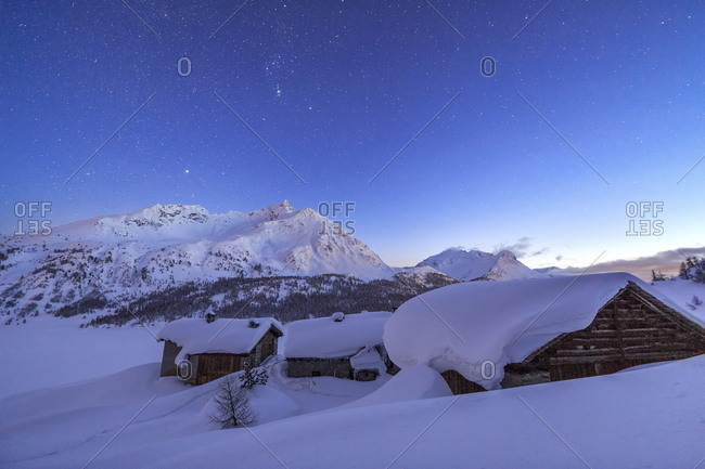 Huts in Spluga covered in thick snow during a clear starry night, Graubunden, Swiss Alps