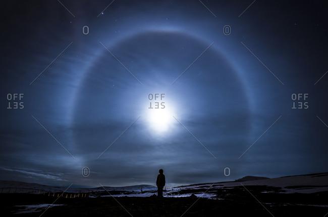 Hiker watching moon's glow over Norwegian mountain