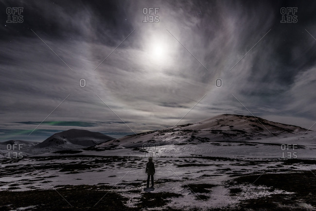 Hiker watching rings of moonlight over Norwegian mountain