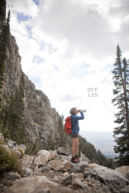 Woman hydrates while hiking in Garnet Canyon, Grand Teton National Park