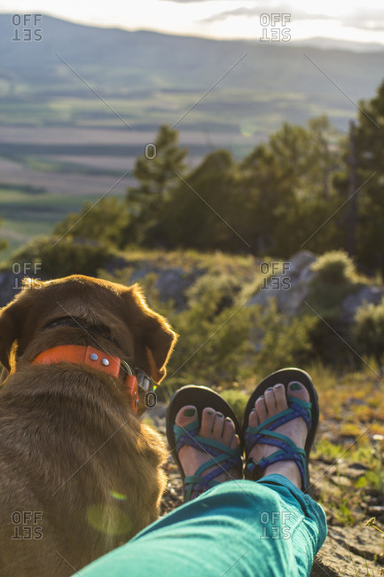 A woman and her dog take a break from hiking to watch the sunset